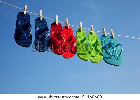 Blue, green, red, turquoise flipflops hanging on a clothes line with the sky in the background - stock photo