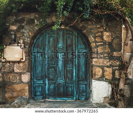 Blue grunge wooden door in brick wall - stock photo