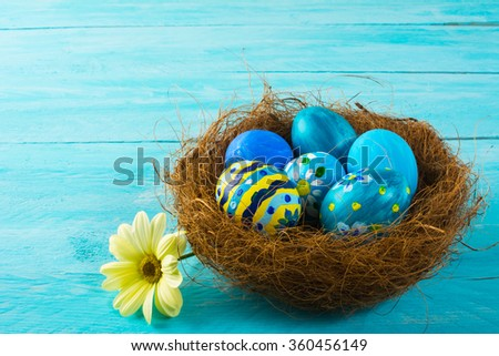 Blue hand-painted decorated Easter eggs in a nest and yellow flower daisy on blue wood plank. Easter background. Easter symbol. Top view with copy space - stock photo