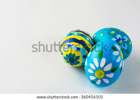 Blue hand-painted Easter eggs with floral design on a white background. Easter background. Easter symbol. Copy space - stock photo