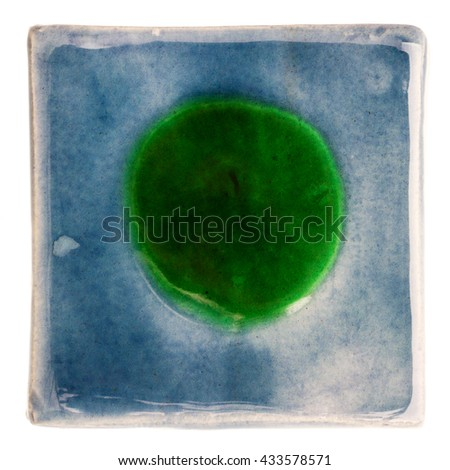 Blue handmade glazed ceramic tile with big green dot in middle isolated on white - stock photo