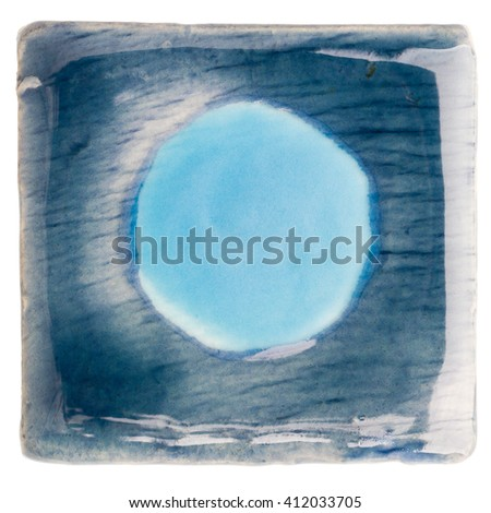 Blue handmade glazed ceramic tile with light blue dot in middle isolated on white