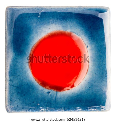 Blue handmade glazed ceramic tile with red dot in middle isolated on white