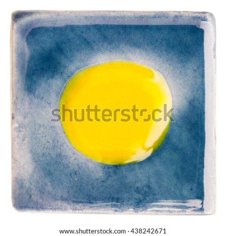 Blue handmade glazed ceramic tile with yellow dot in middle isolated on white - stock photo