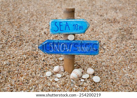 """Blue handmade signpost made of wood and bamboo with the inscription """"sun 10 m, snow 10000 km"""" with shells and shiva eye stones on the coral beach in Thailand. - stock photo"""