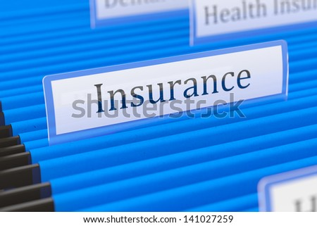 Blue hanging folder with insurance tag on it