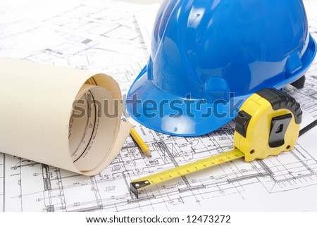 Blue hard hat, yellow pencil, measuring tape and building plans - stock photo