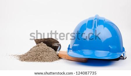 blue hardhat, sand pile and mason trowel - stock photo