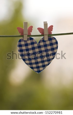 blue heart attached to a clothesline with pin - stock photo