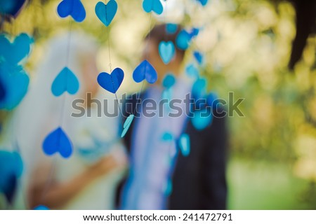 Blue heart in the foreground. High key blurred image of the couple. Unrecognizable faces, bleached effect. - stock photo