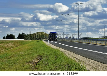 Blue heavy truck with container on the road at the sunny day. - stock photo