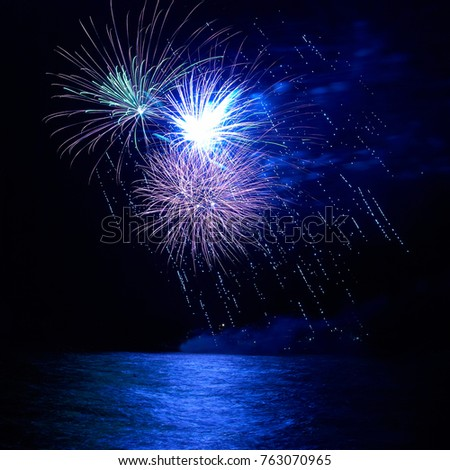 Blue holiday fireworks above lake with water reflection and black sky