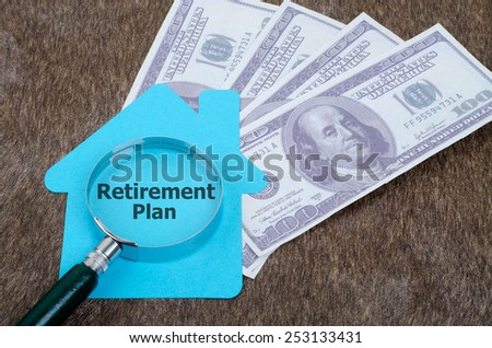 Blue home sign with magnifying glass and money: Retirement plan - stock photo