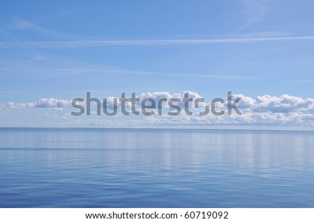 Blue Horizon at sea with white clouds. - stock photo