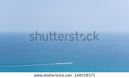 blue horizontal seascape with small speed boat - stock photo