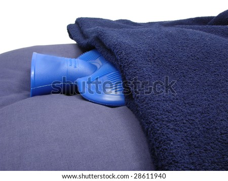 Blue hot-water bag wrapped in a blue blanket on a blue pillow - stock photo