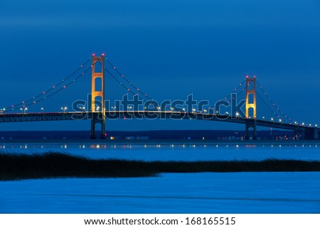 Blue Hour, just after sunset, creates an inviting backdrop for the Mackinac Bridge. Its lights twinkle and create reflections on winter ice. Snow and grass in the foreground add to this fine art photo - stock photo