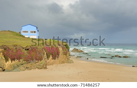 Blue house at northern spain seashore - stock photo
