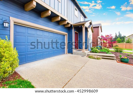 Blue house exterior. View of garage with concrete floor driveway and porch with red entrance door. - stock photo
