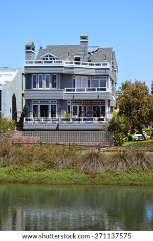 Blue house with a veranda on the shore of the lagoon. Marina del Rey, California.