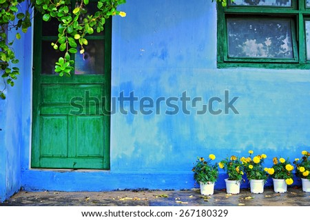 Blue house with green wooden window and door and yellow flowers - stock photo