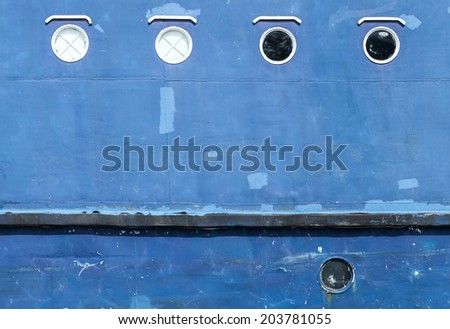 Blue hull of an old ship texture with round portholes - stock photo