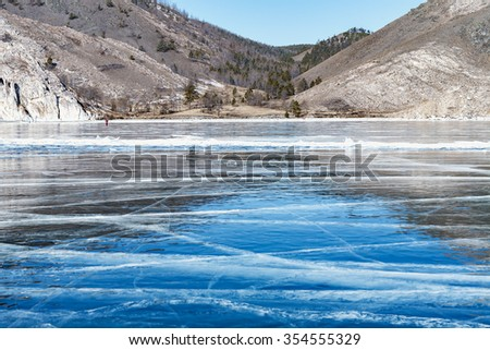 Blue ice and cracks on the surface of the ice. Frozen lake under a blue sky in winter. Mountains and hills with pine trees. Lake Baikal, Siberia, Russia. Horizon. Winter. Cracks