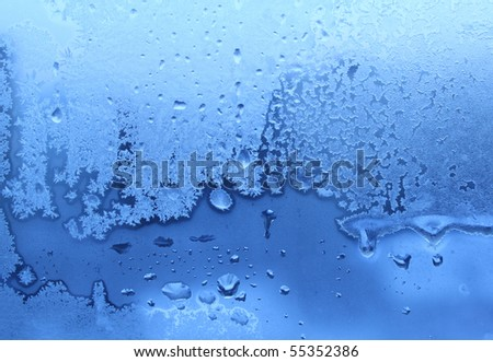 blue ice and water drops on winter glass - stock photo