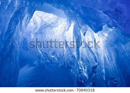 blue ice cave covered with snow and flooded with light - stock photo