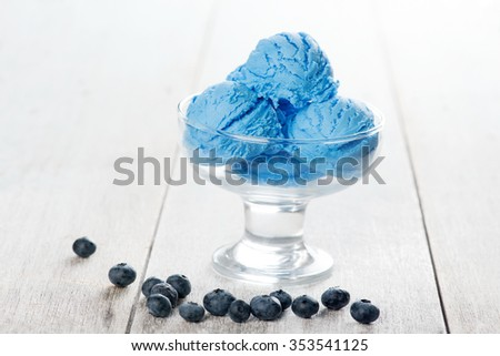 Blue ice cream in cup with blueberry fruits on white rustic wooden background. - stock photo