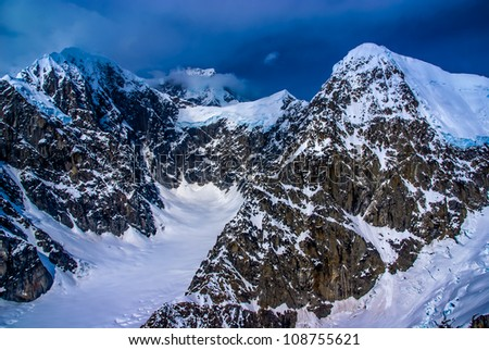 Blue Ice Glacier Headwaters and Snow-pack on Craggy Mountain Peaks with Dark Ominous Clouds.  Aerial View of Denali National Park, Alaska.  A Beautiful Wilderness Snowscape of Rock, Snow, and Ice.
