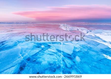 Blue ice of Baikal lake under pink sunset sky - stock photo
