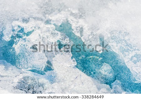 Blue ice on the frozen lake. Macro image with small depth of field - stock photo