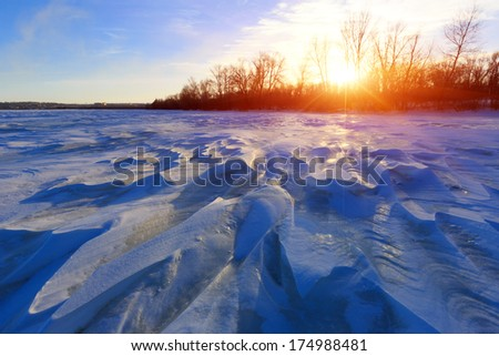 blue ice on winter river against sunset background