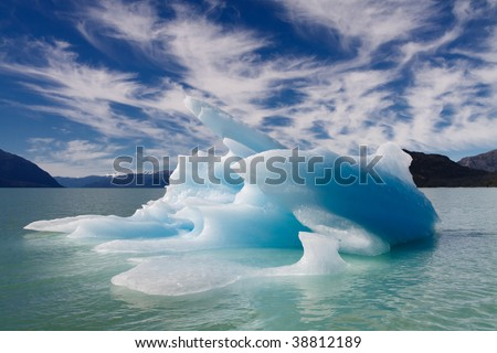 Blue iceberg floating in a fjord in Patagonia, Chile. Dramatic cloud formations and blue sky. - stock photo
