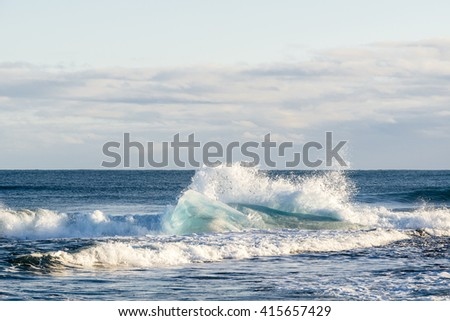 Blue iceberg in the big waves is on the Atlantic ocean near Jokulsarlon glacier lake lagoon. Vatnajokull National Park. Iceland