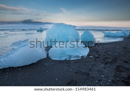 blue icebergs floating near Jokulsarlon glacial lagoon beach at sunset, Iceland