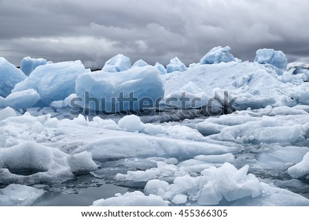 Blue icebergs floating the glacial lagoon in southeast Iceland in summer, blue water in the foreground with copy space and mountains and glacier in the background. - stock photo