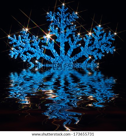 blue illuminated artificial snowflake with lots of twinkling light effects over mirroring water surface in black back - stock photo