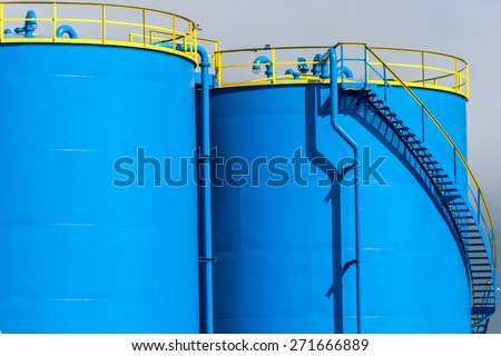 Blue industrial chemical tanks - stock photo