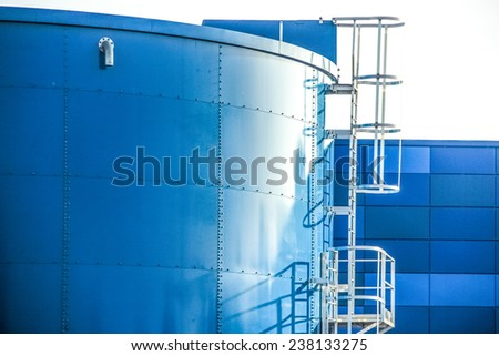 Blue industrial oil container with stairs in a refinery. - stock photo