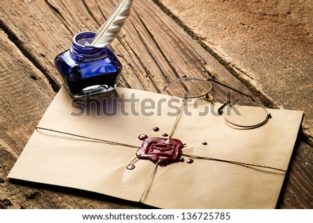 Blue ink inkwell and envelope with red sealant - stock photo