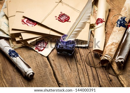 Blue inkwell and glasses surrounded by ancient messages and envelopes - stock photo