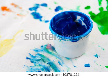 Blue jar of finger paint on a painting - stock photo