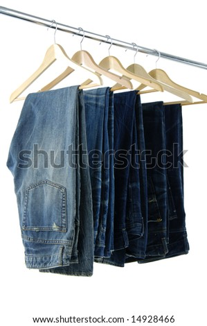 Blue jeans and trousers on wooden hangers - stock photo