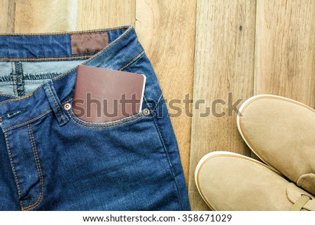 Blue jeans, casual shoes,and passport with wooden background - stock photo