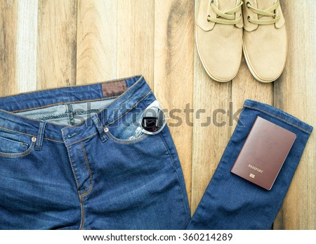 Blue jeans, casual shoes,sunglasses and passport with wooden background - stock photo
