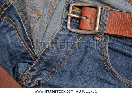 Blue jeans front detail, zipper, pocket and brown leather belt. Fashion and Denim trends - stock photo