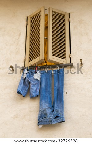 Blue jeans hanging to dry outside shuttered window