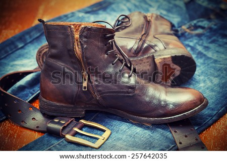 Blue jeans, high leather boots, leather belt with buckle - stock photo